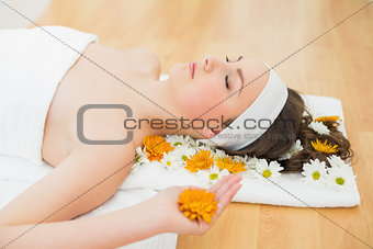 Beautiful woman with eyes closed and flowers in beauty salon