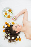 Beautiful woman lying with bowl of flowers in beauty salon