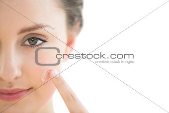 Beautiful young woman applying cream to her face