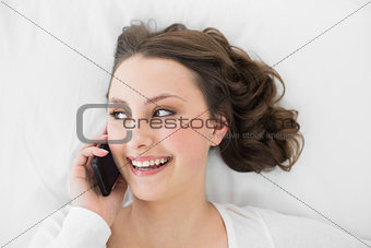 Young brunette using mobile phone in bed