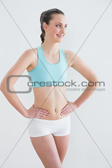 Toned young woman standing against wall