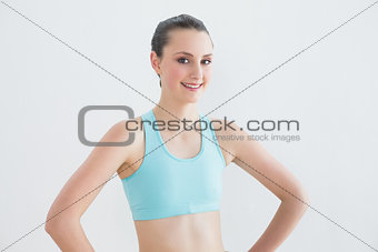 Smiling toned woman with hands on hips against wall