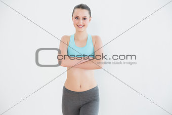 Portrait of toned woman standing against wall