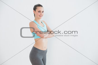 Portrait of toned woman against wall