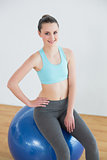 Fit woman sitting on exercise ball in fitness studio