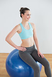 Smiling fit woman on exercise ball in fitness studio
