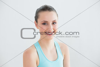 Close up of smiling toned woman against wall