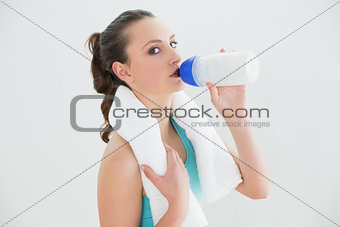 Portrait of fit woman drinking water at the gym
