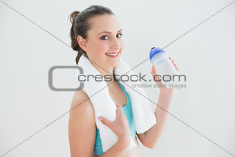 Fit woman with water bottle against wall