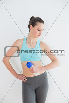 Toned woman holding water bottle against wall