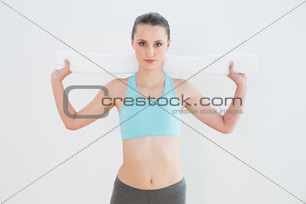 Fit woman with towel around neck against wall