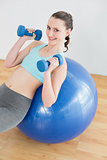 Woman with dumbbells on exercise ball in fitness studio
