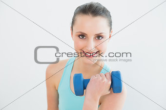 Portrait of woman with dumbbell against wall