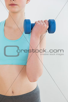 Close up mid section of woman with dumbbell