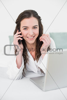 Casual woman using cellphone and laptop in bed