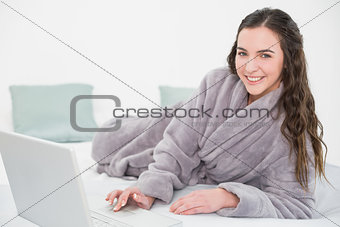 Relaxed brunette in bathrobe using laptop in bed