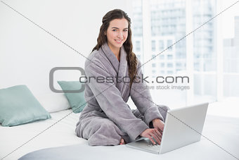 Smiling brunette in bathrobe using laptop in bed