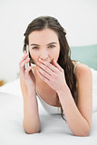 Shocked young woman using mobile phone in bed