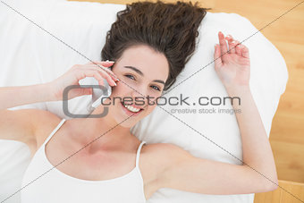 Portrait of relaxed woman using mobile phone in bed