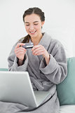 Casual woman in bathrobe doing online shopping in bed