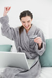 Excited woman in bathrobe doing online shopping in bed