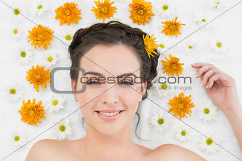 Beautiful young woman with flowers in beauty salon