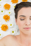 Beautiful young woman with eyes closed and flowers in beauty salon