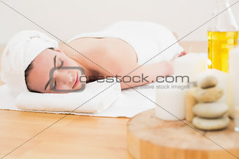 Beautiful woman and oil bottle at beauty spa