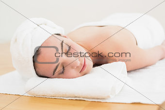 Beautiful woman with eyes closed on towel at beauty spa