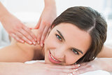 Smiling woman enjoying shoulder massage at beauty spa