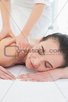 Beautiful woman enjoying shoulder massage at beauty spa