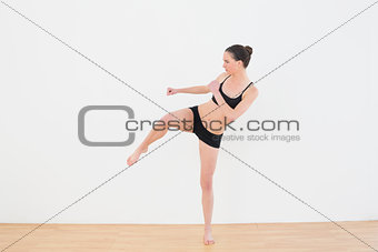 Sporty fit woman performing an air kick in fitness studio