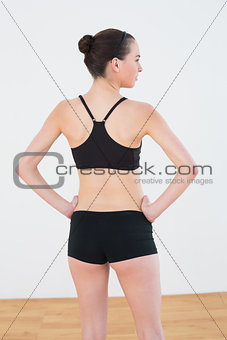 Toned woman against wall in fitness studio