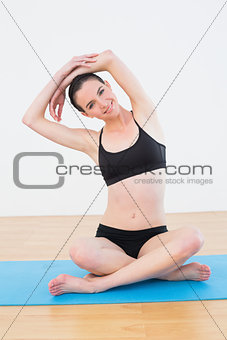 Toned woman stretching hands over head in fitness studio