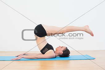 Fit woman doing plough posture in fitness studio