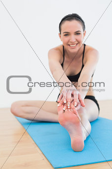 Cheerful woman stretching leg in fitness center