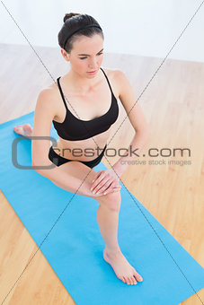 Fit woman stretching leg in fitness center