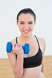 Smiling young woman with dumbbell at fitness studio