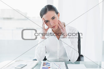 Portrait of worried businesswoman with graphs at office