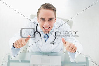 Overhead portrait of smiling doctor with laptop gesturing thumbs up