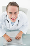 Overhead portrait of a smiling male doctor using laptop