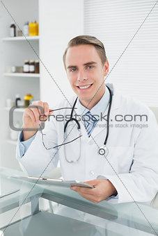 Smiling male doctor with digital tablet at medical office
