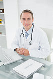 Smiling male doctor with laptop at medical office