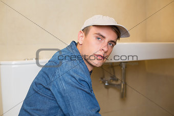 Serious male plumber by the sink