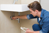 Handsome plumber with wrench by sink in bathroom
