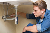 Handsome plumber repairing washbasin drain in bathroom