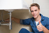Handsome plumber gesturing thumbs up besides washbasin drain