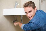 Smiling plumber repairing washbasin drain