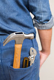 Several tools in a man's rear denim pocket