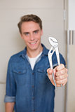 Smiling young handyman holding out wrench